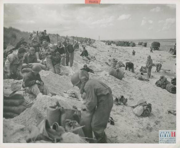 Hitting the beach' along with Army troops, members of a U. S. Navy beach battalion dig in for their first night ashore on a beachhead on the French coast. U.S. Navy Official photograph, Gift of Charles Ives, from the collection of The National WWII Museum