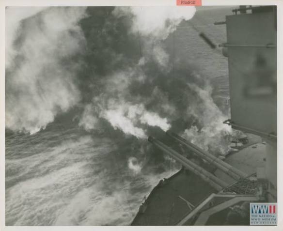 Flame and smoke gush from the muzzles of 14-inch guns as the U.S.S. Nevada pours an obliterating hail of death on Nazi positions blocking the forward surge of Allied troops in France. U.S. Navy Official photograph, Gift of Charles Ives, from the collection of The National WWII Museum.
