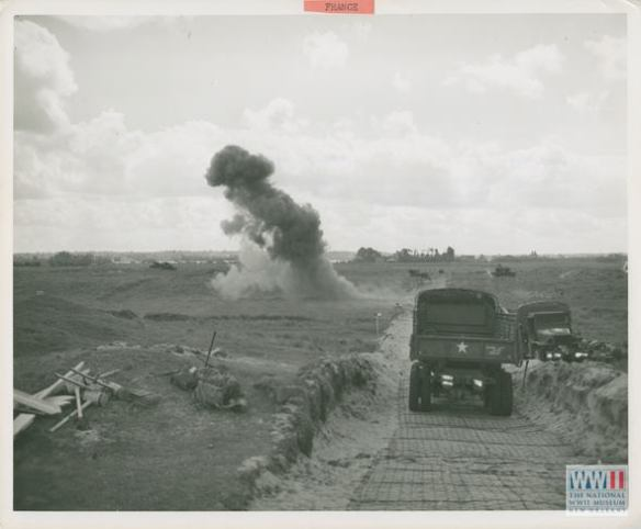 Smoke rises from a roadside in France as Army shore engineers explode Nazi land mines to clear the path for advancing Allied forces racing ahead to extend beachhead holdings. U.S. Navy Official photograph, Gift of Charles Ives, from the collection of The National WWII Museum.