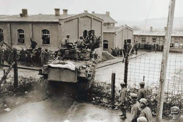 A US Army M4 Sherman tank of the 47th Tank Battalion, 14th Armored Division, crashes through the fence of Oflag XIII-B, April 6, 1945.