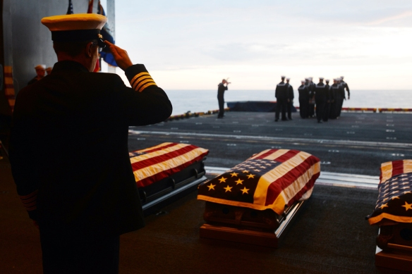 Atlantic Ocean, December 6, 2014. Capt. John Carter, commanding officer of the amphibious assault ship USS Bataan (LHD 5) salutes during a burial-at-sea.  Bataan is conducting an underway evolution in preparation for an upcoming planned maintenance availability.  U.S. Navy photo by Mass Communication Specialist 1st Class Julie Matyascik