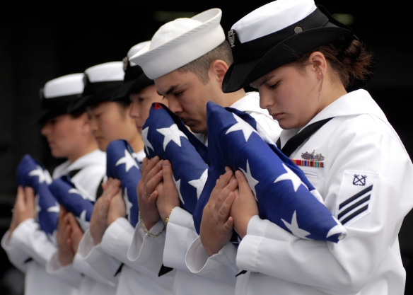 Pacific Ocean, August 19, 2007. US Navy flag bearers bow their heads in prayer during a burial at sea ceremony aboard Nimitz-class aircraft carrier USS Abraham Lincoln (CVN 72). Lincoln conducted the solemn and sacred tradition of burial at sea for 11 former service members during her transit home to Everett, Washington. Lincoln completed carrier qualifications, Tailored Ship's Training Availability and Final Evaluation Problem during a scheduled work-up off the coast of Southern California.  U.S. Navy photo by Mass Communication Specialist 3rd Class James R. Evans.