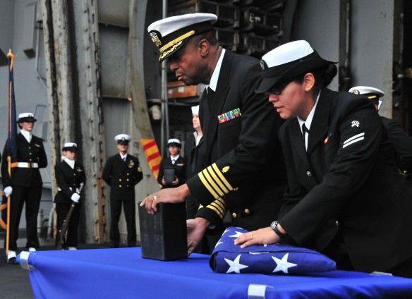 Arabian Sea, April 9, 2011. Sailors aboard the aircraft carrier USS Enterprise (CVN 65) prepare to cast ashes overboard during a burial at sea.  Enterprise and Carrier Air Wing (CVW) 1 are conducting close-air support missions in the U.S. 5th Fleet area of responsibility.  U.S. Navy photo by Mass Communication Specialist Seaman Jesse L. Gonzalez.