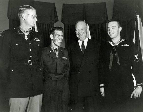 President Dwight D. Eisenhower poses with three men to whom he has just presented the Medal of Honor for conspicuous gallantry in Korean War combat action, at the White House, Washington, D.C., 12 January 1954. Those who received the medal are (from left to right): First Lieutenant Edward R. Schowalter, Jr., U.S. Army, honored for his actions near Kumhwa, Korea, on 14 October 1952; Private First Class Ernest E. West, U.S. Army, honored for his actions near Sataeri, Korea, on 12 October 1952; and Hospital Corpsman Third Class William R. Charette, U.S. Navy, honored for his actions in Korea on 17 March 1953. Official U.S. Navy Photograph.
