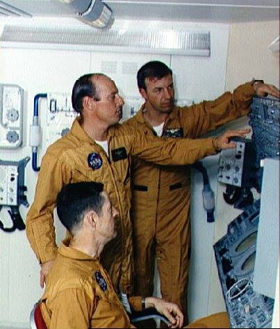 "These three men are the crewmen for the first manned Skylab mission. They are Charles Conrad Jr., commander, standing left; scientist-astronaut Joseph P. Kerwin, seated; and Astronaut Paul J. Weitz, pilot. They were photographed and interviewed during an ""open house"" press day in the realistic atmosphere of the Multiple Docking Adapter (MDA) trainer in the Mission Simulation and Training Facility at the Manned Spacecraft Center (MSC). The control and display panel for the Apollo Telescope Mount (ATM) is at right. NASA Photograph Collection."